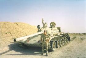 Soldier from 4 PARA poses with an abandoned tank in the desert, Iraq, c.2004
