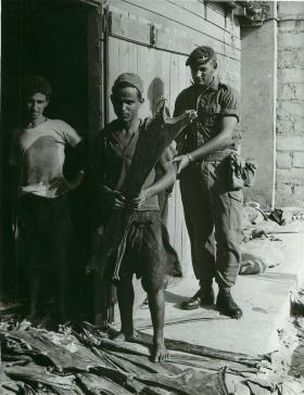 Paratrooper standing behind two locals, Aden, 1960s