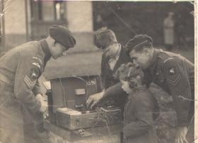 Sgt Ted Parker and colleague demonstrating a radio set to children
