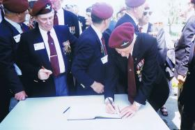 Paul Aller signs the Mayors book, having been given Freedom of Benouville, June 1996