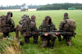 Pathfinders provide cover, with a Merlin helicopter in the background, on exercise in the UK, c2008.