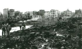 Locals examine the destruction of buildings in Port Said. Fires burn in the background.