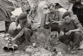 Privates Healy, Collins and Bowman crouch by a fire and make their cap badges at time of their introduction.