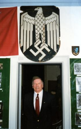 Stan Clitherow at Fulbeck Hall with Nazi plaque he brought back from Nijmegen in 1944, c1990.
