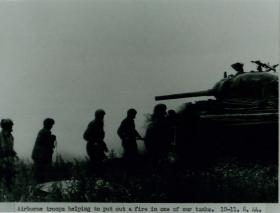 Airborne troops help put out a tank fire.
