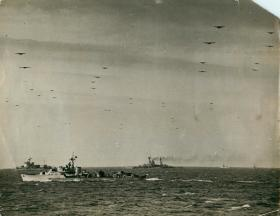 Gliders cross the Channel above ships of the Royal Navy.