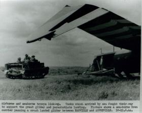 Sea-borne Universal Carrier passes a crash landed glider, June 1944.