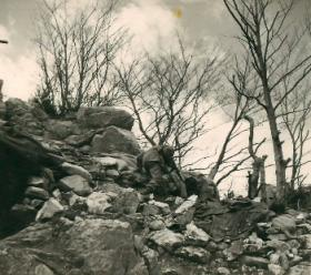 Member of 2nd Parachute Brigade negotiates rocky terrain near Cassino.