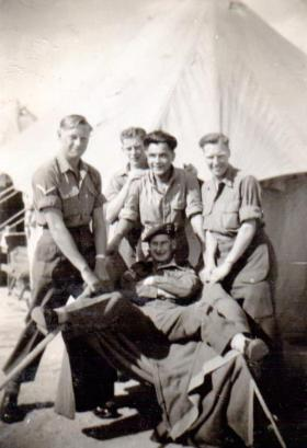 Sgt Goodwin, seated, with friends, 1947.