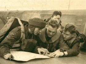 Details of the drop zone are briefed to troops with a map on an aircraft wing.