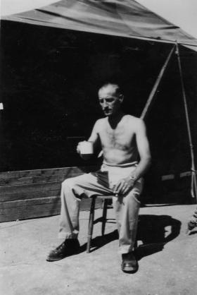 John Alcock seated outside a tented camp, 3rd Para Bn,  Cyprus, c1956.