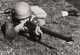 A soldier of the Royal Ulster Rifles takes aim with a Rifle, No.4 Mk I, 1943.