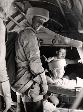 """A para, wearing a """"Sorbo"""" helmet, prepares to jump, RAF Kabrit, c1942."""