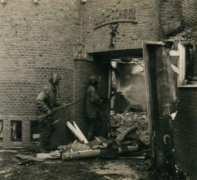 Two paratroopers with Sten guns enter a destroyed school.