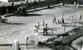 Pte Derrick Frank surrounded by children, Suez, 6 November 1956.