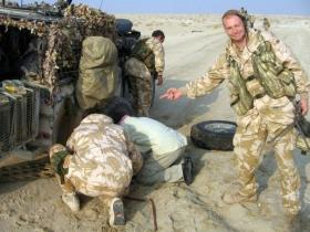 Pte Steve Lewis, 2 PARA, 'helps' with a tyre change, Iraq, 2005.