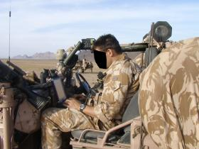 Using a laptop in a WMIK, Nowzad, Afghanistan, Op Herrick IV, 2006.