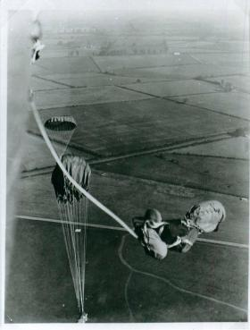 Paratrooper has just exited the aircraft. He holds a container and is attached to the plane by his release strop.
