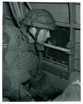 Paratrooper looks out a Douglas Dakota aircraft window for briefed landmarks on approaching the drop zone.