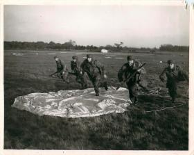 Posed photo of paratroopers ready for action after discarded their parachutes.