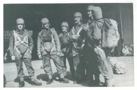 Line of paratroops showing the early parachute smock and experimental head protection.