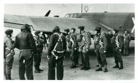 Numbering off of sticks prior to emplaning Whitley aircraft. Aircraft crew look on.