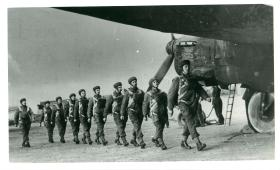 A stick of parachutists march in a line to emplane a Whitley aircraft.