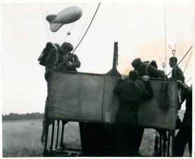 Parachute trainees climb into a balloon cage prior to a training jump.