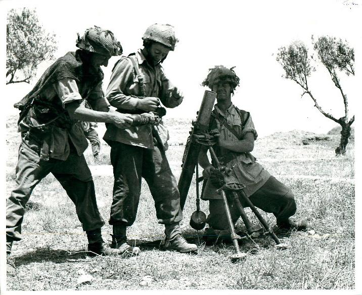 Three men from a 3-inch mortar team loading ammunition, North Africa, 1943