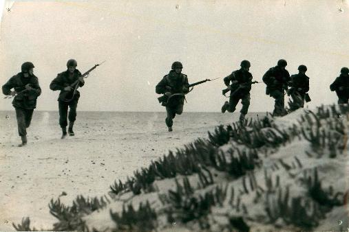 Seven men from 1st Airborne Division run along sandy terrain with guns.