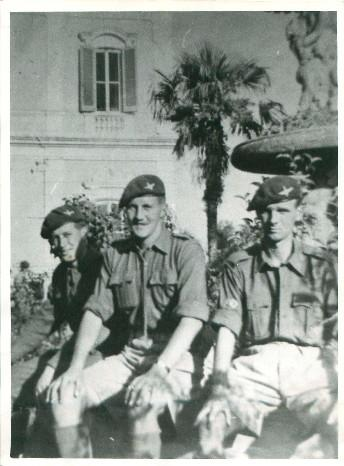 Three officers from A Company 3rd Parachute Battalion sit on a wall in a courtyard.