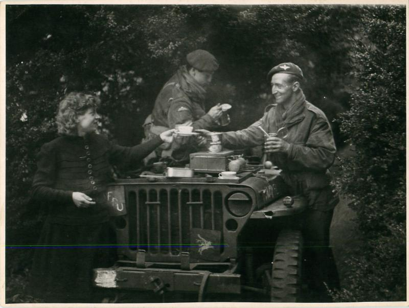 Two correspondents from the   1st Airborne Film Unit drink tea in a jeep.