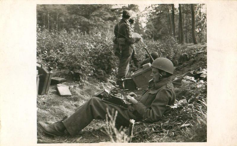 War correpondent Alan Wood sits with a typewriter in grounds of Hartenstein Hotel.