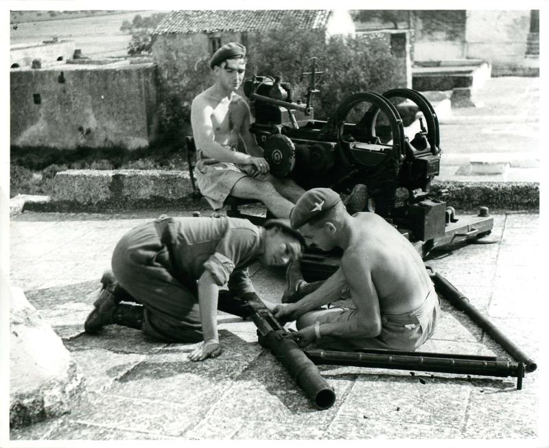 Drivers and batman master the intricacies of a German Flak gun captured in southern France.