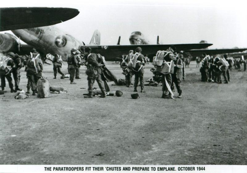 Paratroopers fit their 'chutes and prepare to emplane.