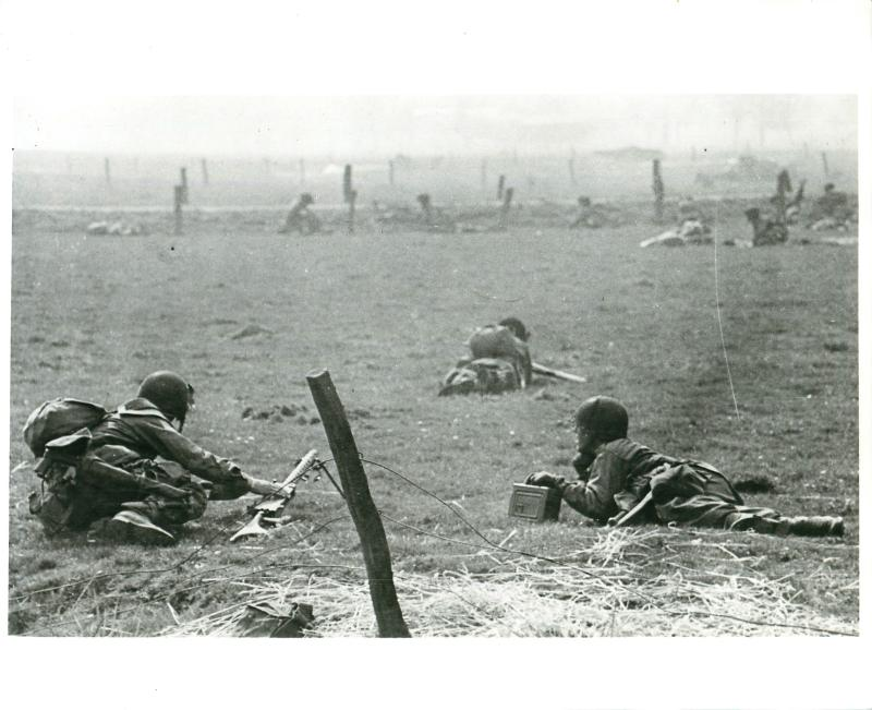 Paratroopers inch along flat ground toward their objective.