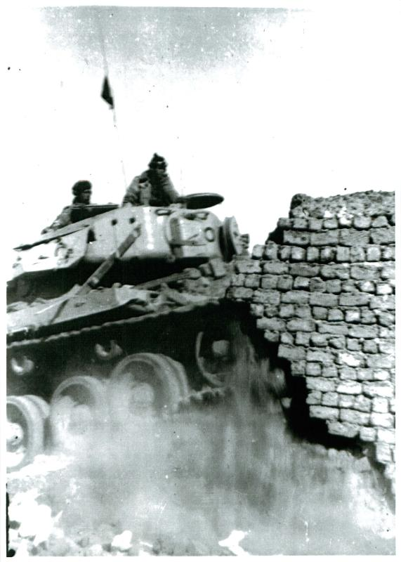 A Centurian tank demolishing houses in Gaynaeim, following trouble from snipers. Canal Zone, Egypt.