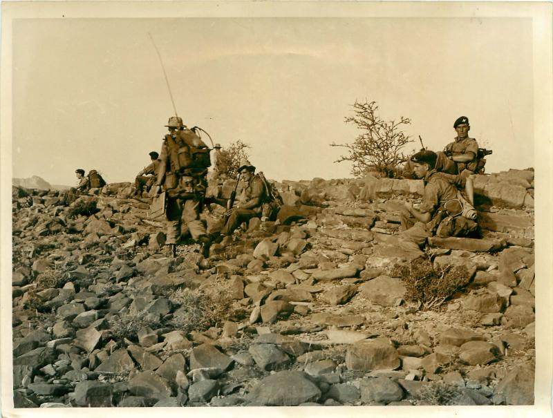 Men of 3 PARA D Company wait to move forward on rocky terrain.