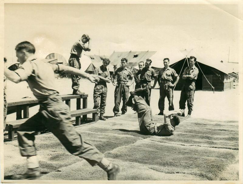 Troops practise parachute rolls on mats as part of synthetic training.
