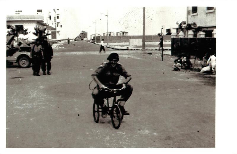 A smiling member of 3 PARA rides a small tricycle through a street in Port Said while locals look on.