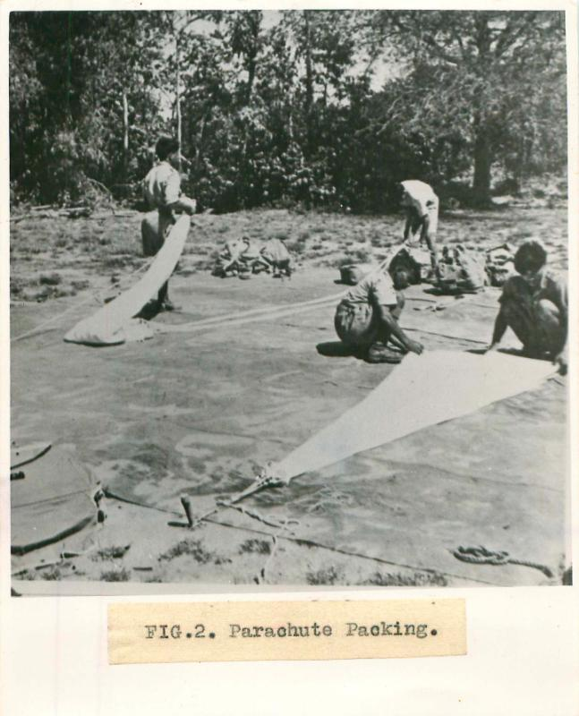 Men from No. 1 Indian Air Company squat on the floor outdoors and pack parachutes.