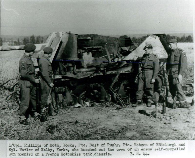 Four paratroopers stand with a burned out Hotchkiss tank chassis.