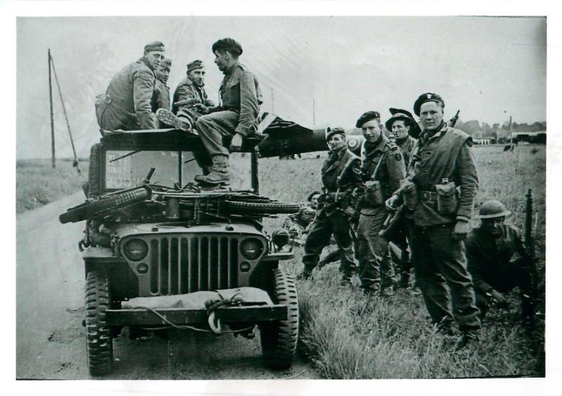 Commandos of 1st Special Service Brigade with captured Germans  on and around a military vehicle near drop zone N.
