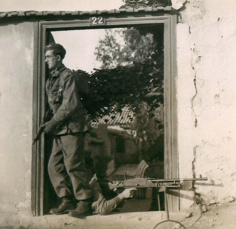 Two paratroopers take up position in the doorway of a building.