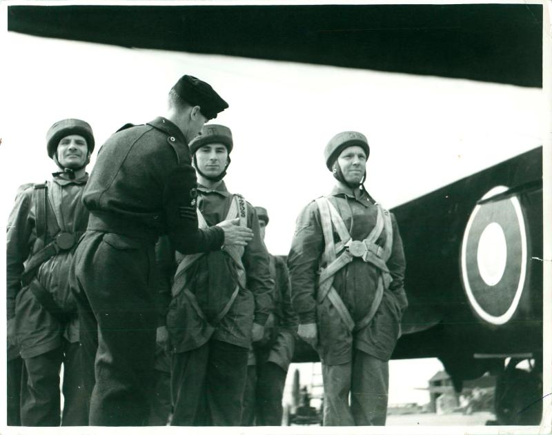 RAF jump instructor makes final checks of parachute harnesses prior to emplaning.